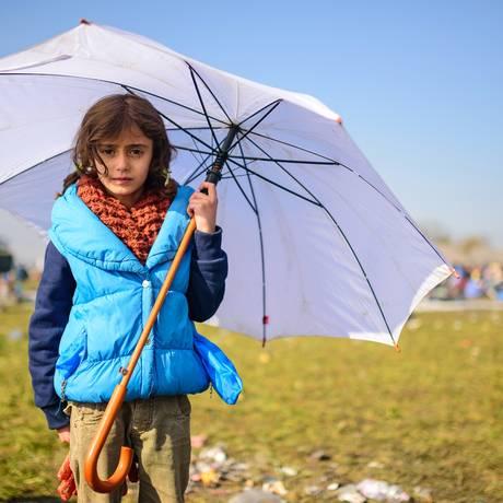 Menina posa para foto enquanto refugiados esperam para atravessar fronteira entre Croácia e Eslovênia Foto: Jure Makovec / AFP