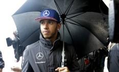 Hamilton se protege da chuva no paddock. Piloto inglês pode ser campeão neste domingo Foto: REUTERS