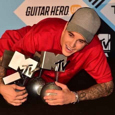 Justin Bieber brinca com seus cinco troféus Foto: GIUSEPPE CACACE / AFP
