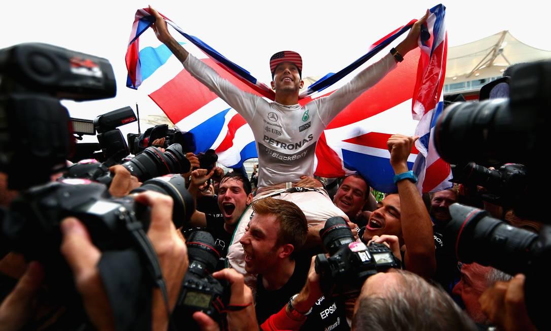 Bandeirão britânico aberto às costas, Hamilton mostra toda sua alegria com a conquista do terceiro título (2008/2014/2015) CLIVE MASON / AFP
