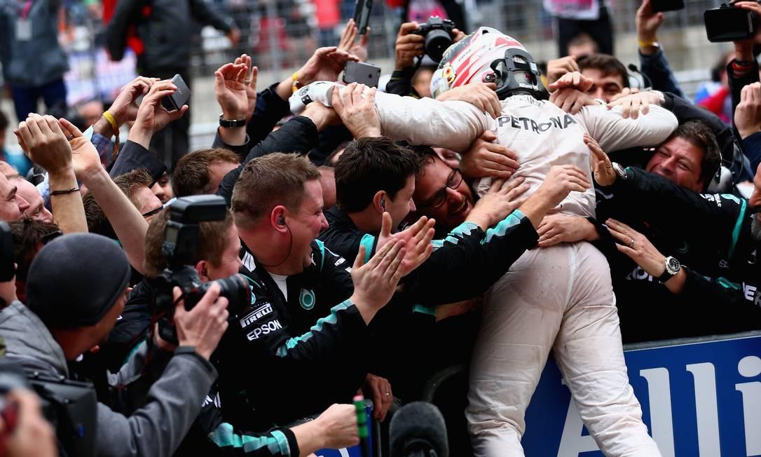 Nos braços dos companheiros de equipe Mercedes, o tricampeão Hamilton festeja antes mesmo de tirar o capacete, assim que deixa o carro CLIVE MASON / AFP