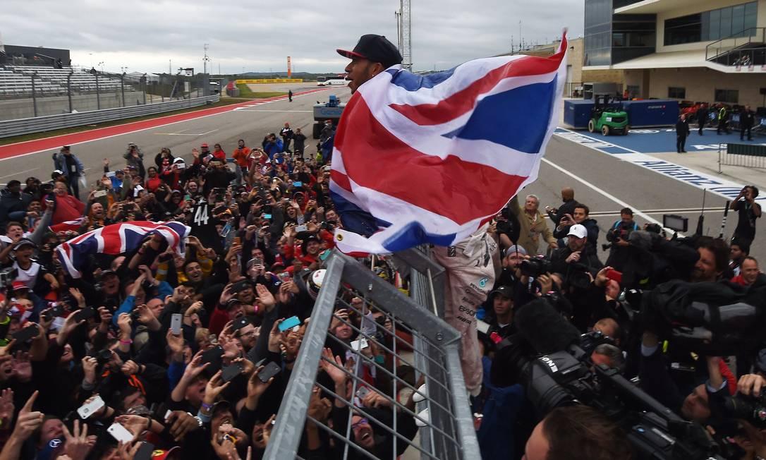 Na foto Hamilton até parece super-herói, a bandeira dá impressão de ser a capa do Super Homem. E vai ver que é, não? MARK RALSTON / AFP