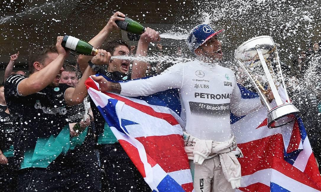 Explosão de champanhe no tricampeão Hamilton Lars Baron / AFP