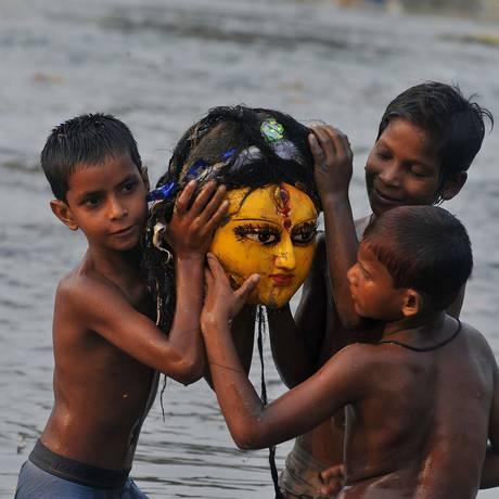 Crianças indianas brincam com cabeça de estátua de divindade hindu: 39% das delas são afetadas por desnutrição no país Foto: DIPTENDU DUTTA / AFP