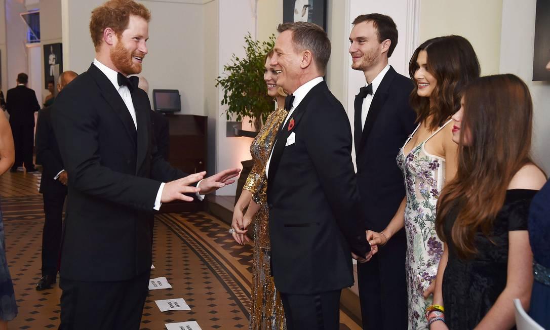 O príncipe Harry engatou um papo animado com os astros do filme. Reparem os papéis no chão com os nomes dos atores. Seria para a realeza não trocar os nomes? POOL / REUTERS