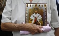 Ativista ortodoxa segura uma imagem de Nicholas 2º, o último czar da Rússia, durante um evento de 2012 em Moscou Foto: Maxim Shemetov/Reuters