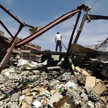 Homem iemenita é visto em meio aos escombros de um depósito depois de ter sido alvo de ataques aéreos realizados pela coalizão liderada Arábia na capital Sanaa Foto: MOHAMMED HUWAIS / AFP