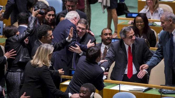 O chanceler Bruno Rodriguez (ao centro) abraça simpatizantes após a votação na ONU Foto: LUCAS JACKSON / REUTERS