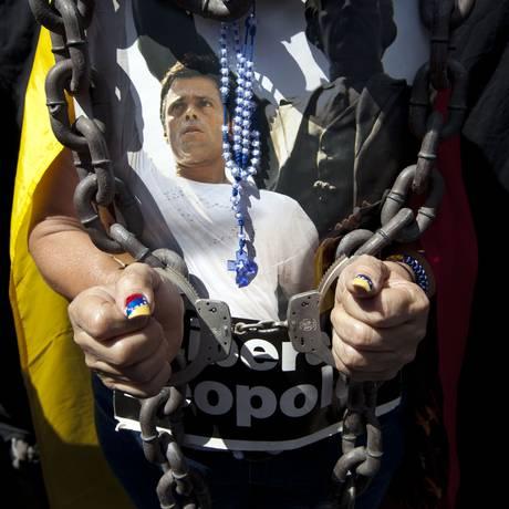 Mulher usando algemas exibe foto de López em evento pelo um ano de prisão do opositor Foto: Ariana Cubillos / AP
