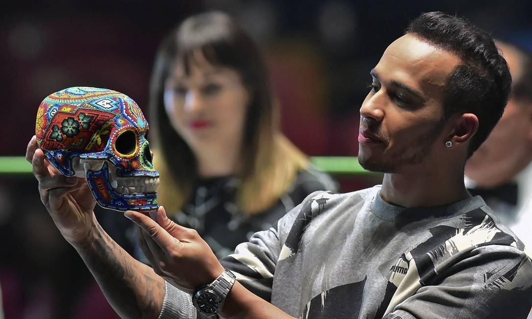 Hamilton bancando o Hamlet com uma típica caveira mexicana decorada. Ser ou não ser tetracampeão na próxima temporada, eis a questão? RONALDO SCHEMIDT / AFP