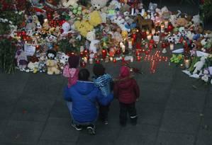 Família deposita flores na entrada do aeroporto de Pulkovo, em São Petersburgo, em homenagem às vitimas do avião que caiu no Sinai com 224 pessoas a bordo Foto: Dmitry Lovetsky / AP