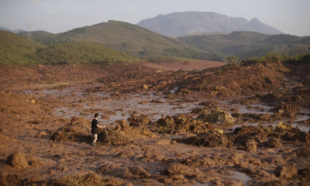 Um homem anda sobre o mar de lama no distrito de Bento Rodrigues após o rompimento de duas barragens Foto: Ricardo Moraes / REUTERS