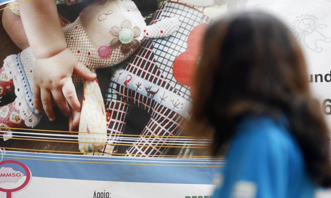 Criança frente a cartaz de campanha sobre violência doméstica e sexual em São Gonçalo: debatia sobre pedofilia e abuso acontece na noite desta segunda no Rio Foto: Marcos Tristão