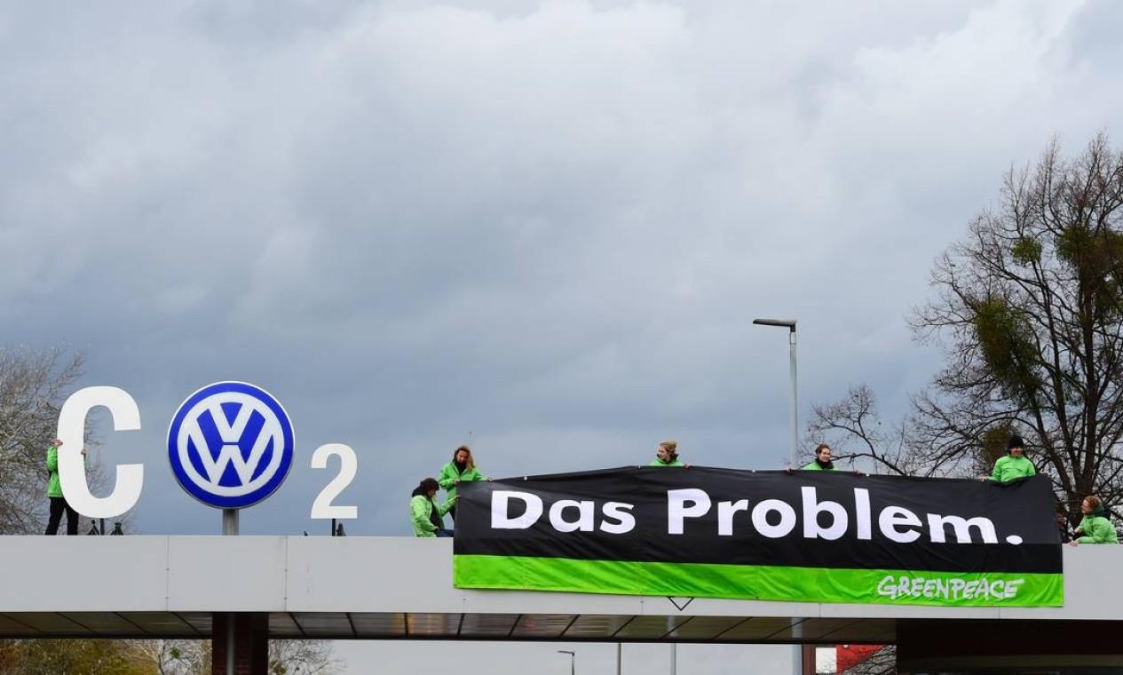 Ativistas do Greenpeace protestam na entrada da fábrica da Volkswagen (VW) em Wolfsburg, região central da Alemanha, em 9 de novembro de 2015. A associação de consumidores da Alemanha quer que a gigante automotiva Volkswagen ofereça vouchers como forma de compensação aos clientes alemães afetados pelo escândalo maciço de fraude na fiscalização de poluentes emitidos pelos veículos do grupo Foto: JOHN MACDOUGALL / AFP