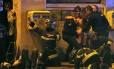 Massacre. Bombeiros socorrem feridos emfrente à casa de shows Bataclan: terroristas dispararam contra o público