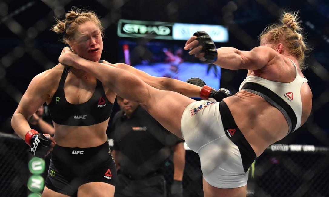 Holly Holm atinge chute alto poderoso na então campeã Ronda Rousey no 2º round da luta pelo cinturão do peso-galo feminino no UFC 193. Foi o golpe que definiu o combate a favor da desafiante PAUL CROCK / AFP