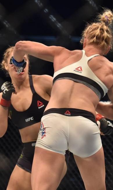 A bomba de canhota de Holly Holm encontra o rosto de Ronda Rousey em mais um lance em que machucou a então campeã do peso-galo do UFC PAUL CROCK / AFP