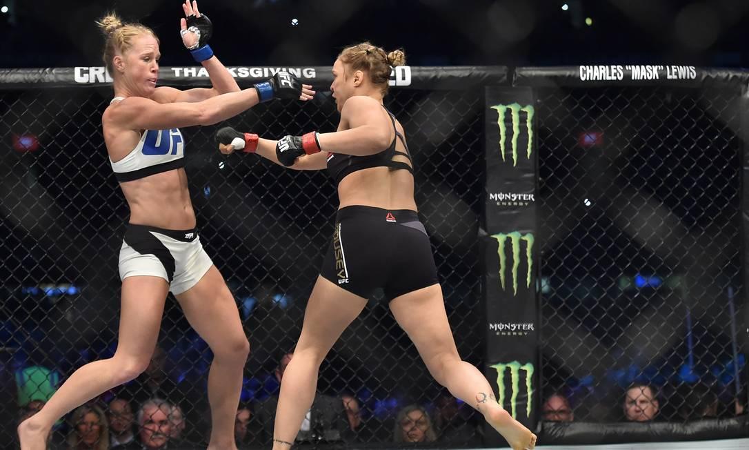 Holly Holm mostra agilidade e se esquiva com rapidez da investida de Ronda Rousey, que passa no vazio e vai de encontro à grade do octógono PAUL CROCK / AFP