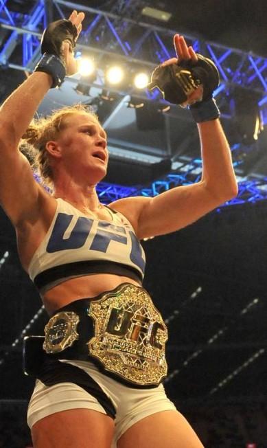 Coroada nova rainha do UFC, Holly Holm comemora com o cinturão do peso-galo, que até este dia tinha tido apenas uma dona, Ronda Rousey PAUL CROCK / AFP