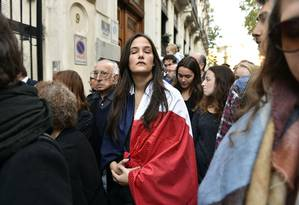 Uma mulher se enrola numa bandeira da França, em uma homenagem Às vítimas em Madri Foto: GERARD JULIEN / AFP