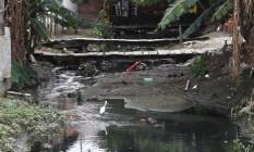Pequenas pontes foram construídas irregularmente sobre o assoreado Rio Jacaré para dar acesso às casas também instaladas ali ilegalmente Foto: Pedro Teixeira / Agência O Globo