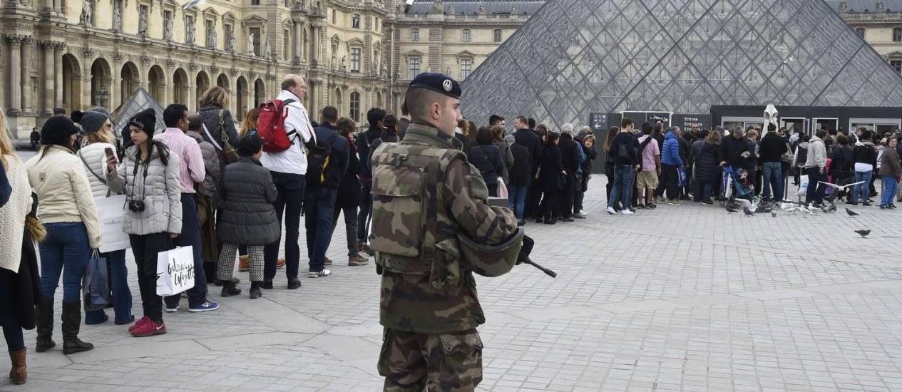 Soldado francês reforça segurança em frente ao Museu do Louvre, enquanto visitantes fazem fila Foto: DOMINIQUE FAGET/AFP