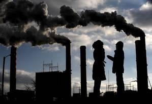 Mulheres polonesas conversam em frente à usina: países desenvolvidos não pagam valores justos para atenuar mudanças climáticas, diz ONG Foto: JOE KLAMAR/AFP