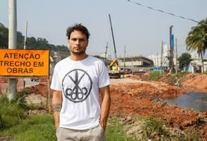 Rodrigo Macniven em frente à Vila Autódromo, vestindo a camisa com a estampa do filme Foto: Barbara Lopes / Agência O Globo