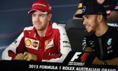 Superastros. O alemão Sebastian Vettel, da Ferrari, tetracampeão mundial, e o inglês Lewis Hamilton, da Mercedes, tricampeão, sorriem durante entrevista coletiva na Austrália. A dupla vem dominando a F-1 Foto: William West/AFP/12-03-2015