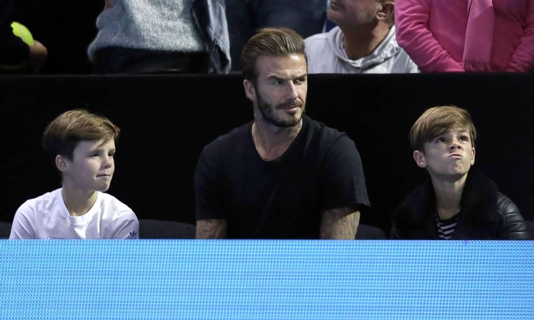 Depois de ser eleito o homem mais sexy do mundo, David Beckham mostra sua versão paizão em jogo de tênis. Ao lado de Cruz (à esquerda) e Romeo, o ex-jogador acompanhou a semifinal entre Novak Djokovic e Rafael Nadal no ATP World Tour, em Londres, neste sábado Tim Ireland / AP