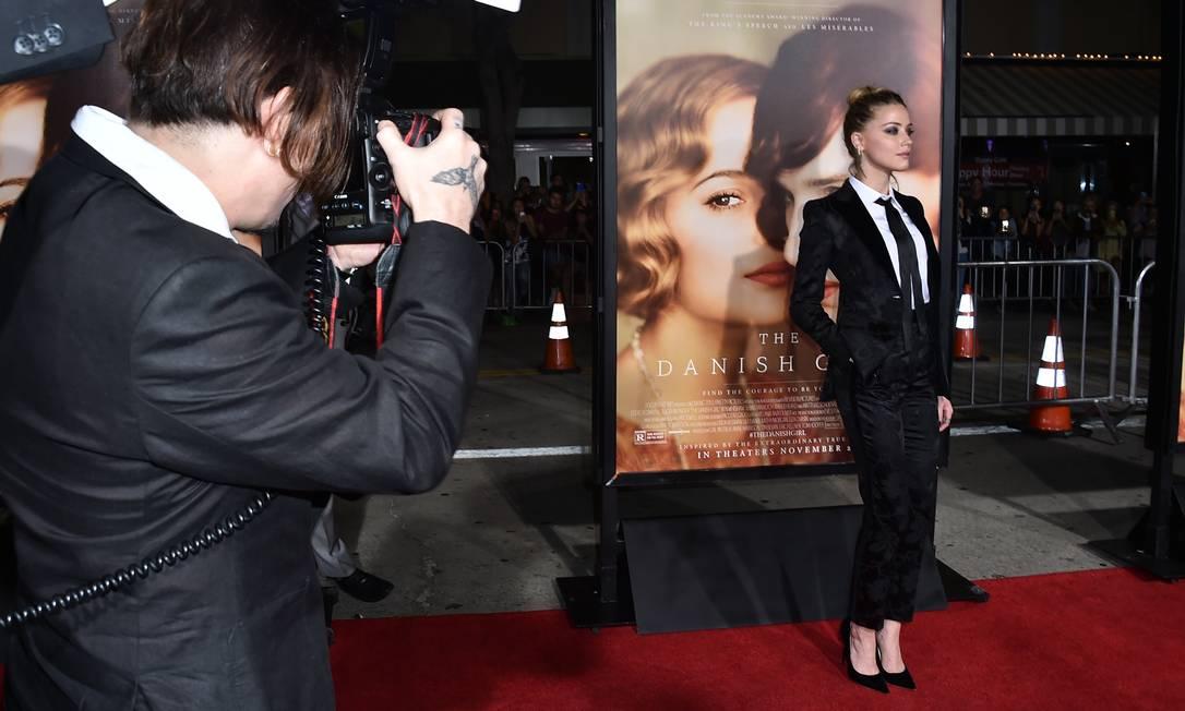 Durante a passagem de Amber Heard pelo tapete vermelho, Johnny Depp pegou a câmera de um fotógrafo e clicou a mulher Jordan Strauss / Jordan Strauss/Invision/AP