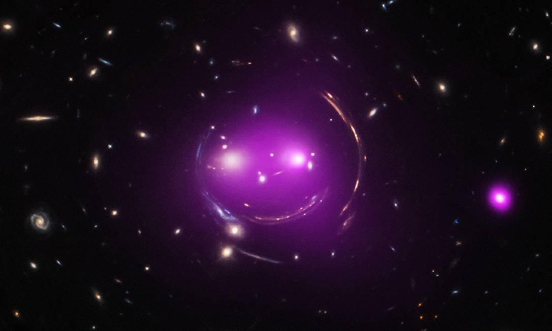 """Combinação de observações feitas com os telescópios espaciais Hubble (luz visível) e Chandra (raios-X) mostra os grupos de galáxias que formam um sorriso no céu e por isso receberam o apelido de """"Gato de Cheshire"""", personagem do livro """"Alice no País das Maravilhas"""": estudo indica que as galáxias que formam os """"olhos"""" do gato estão se aproximando a uma velocidade de cerca de 500 mil km/h e devem se fundir dentro de 1 bilhão de anos Foto: / Nasa/Chandra/Hubble"""