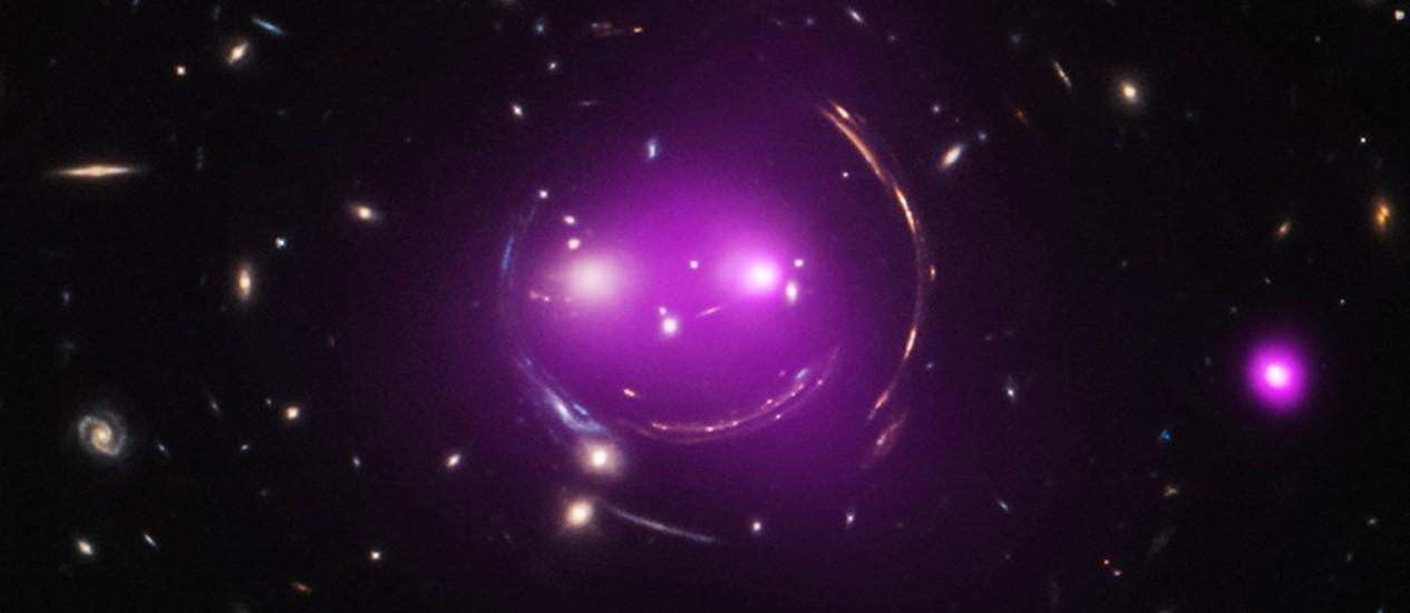 """Combinação de observações feitas com os telescópios espaciais Hubble (luz visível) e Chandra (raios-X) mostra os grupos de galáxias que formam um sorriso no céu e por isso receberam o apelido de """"Gato de Cheshire"""", personagem do livro """"Alice no País das Maravilhas"""": estudo indica que as galáxias que formam os """"olhos"""" do gato estão se aproximando a uma velocidade de cerca de 500 mil km/h e devem se fundir dentro de 1 bilhão de anos Foto: Nasa/Chandra/Hubble"""