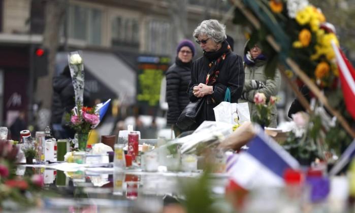 Milhares de pessoas depositaram flores e velas para lembrar as vítimas do massacre THOMAS SAMSON / AFP