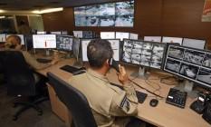 Agente da Seop recebe os chamados enquanto monitora as câmeras Foto: Luiz Ackermann / Agência O Globo