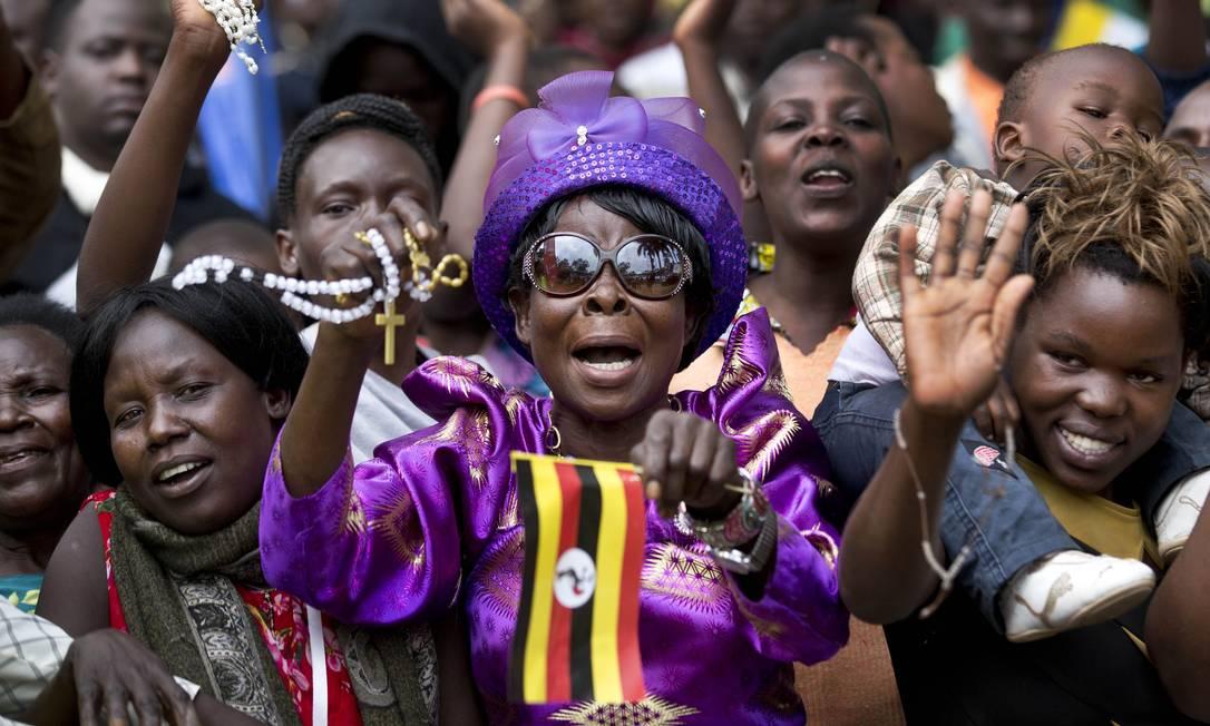 Mulher segura terço e uma bandeira de Uganda enquanto espera o Papa na Santa Missa para os Mártires de Uganda Ben Curtis / AP