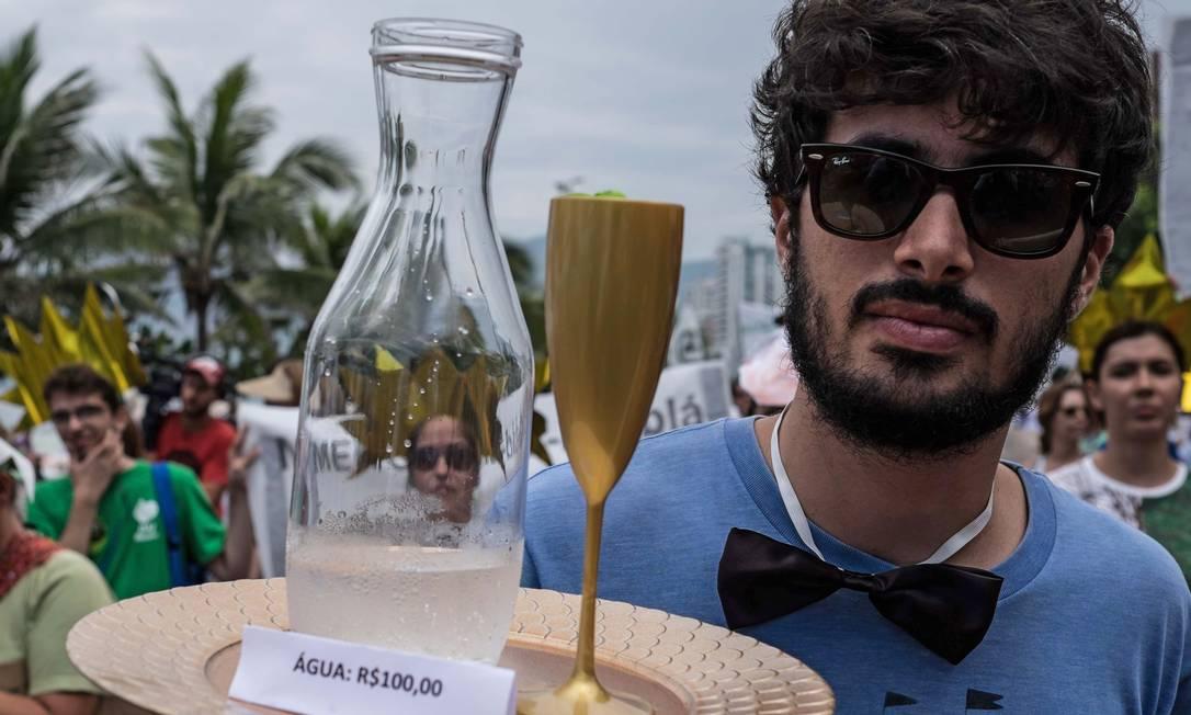 """Em Ipanema, manifestante faz crítica ao """"preço"""" da água: R$ 100 (cerca de US$ 26) CHRISTOPHE SIMON / AFP"""