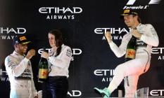 Rosberg comemora a vitória em Abu Dhabi enquanto Hamilton recebe o champanhe. Foi a 12ª dobradinha da Mercedes no ano Foto: MARWAN NAAMANI / AFP