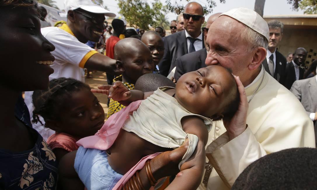 Papa Francisco beija um bebê durante visita a um campo de refugiados, em Bangui, na República Centro Africana Andrew Medichini / AP