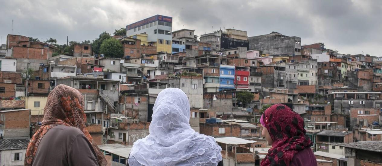 Usando os tradicionais véus, mulheres muçulmanas observam a comunidade do terraço de uma casa na periferia de São Paulo: islamismo vem crescendo no país no rastro da mensagem de igualdade racial e justiça social Foto: Edilson Dantas / Agência O Globo