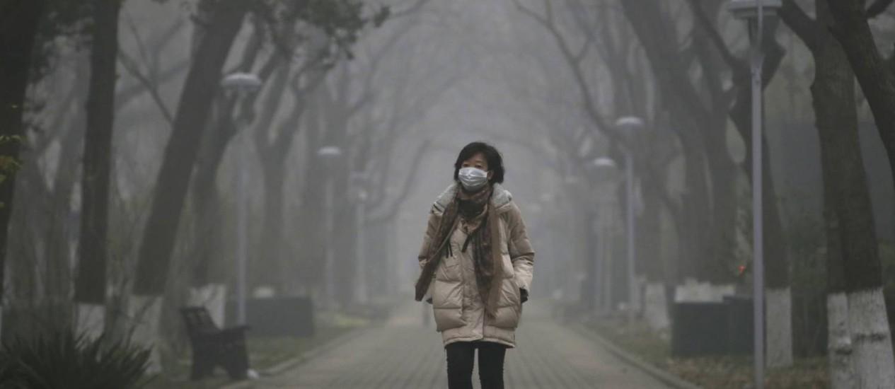 Mulher usa máscara enquanto caminha em meio à névoa em Pequim Foto: JASON LEE / REUTERS