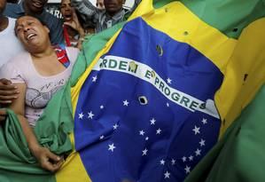 Lágrimas. Mônica, mãe de Cleiton, junto a uma Bandeira Nacional com furos como se fossem marcas de tiros Foto: Domingos Peixoto / O Globo