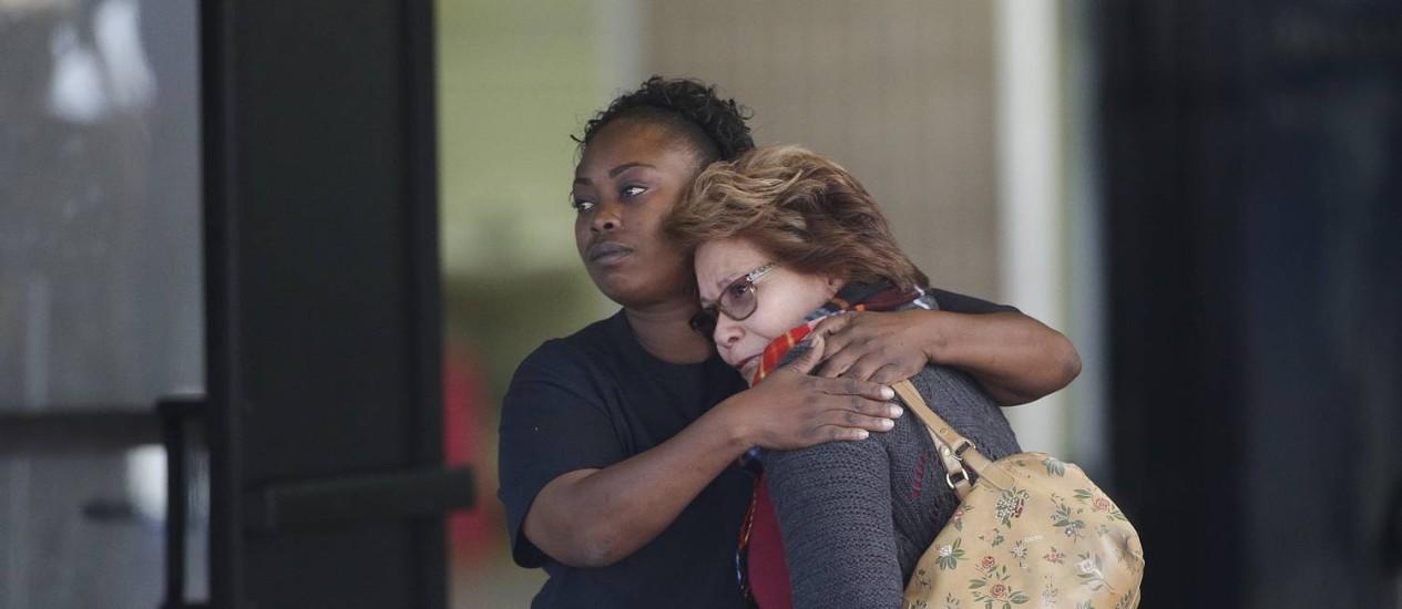 Apreensão. Duas mulheres se abraçam em um centro comunitário que recebeu famílias das vítimas em San Bernardino: questão divide mesmo os partidos Foto: Jae C. Hong / AP