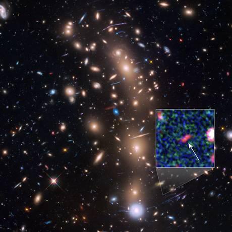 A imagem do Hubble do aglomerado de galáxias MACS J0416.1-2403 com destaque para a pequena galáxia Tayna, cuja luz foi ampliada pelo fenômeno das lentes gravitacionais ao cruzar a região do espaço do primeiro Foto: Nasa/ESA/Leopoldo Infante