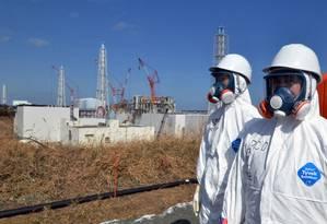 Funcionários de empresa de energia elétrica passam em frente a reator da usina nuclear de Fukushima Foto: AFP/YOSHIKAZU TSUNO/28-02-2012