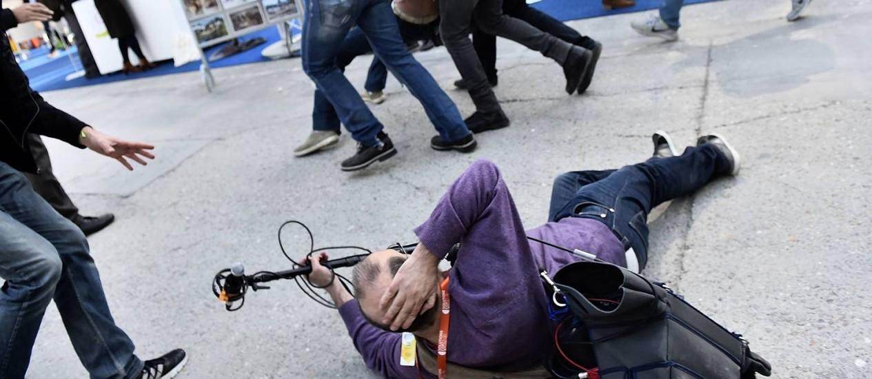 Jornalista cai no chão após policiais evacuarem protestos em Paris durante a COP 21 Foto: LOIC VENANCE / AFP