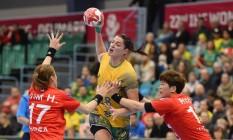 Eduarda Taleska enfrenta a marcação de duas sul-coreanas no ataque do Brasil na estreia no Mundial de handebol Foto: JONATHAN NACKSTRAND / AFP