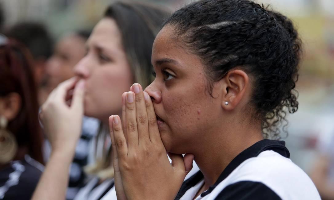 A torcedora junta as mãos numa oração durante o jogo, assistindo pela TV: a fé não foi suficiente Márcio Alves / Agência O Globo