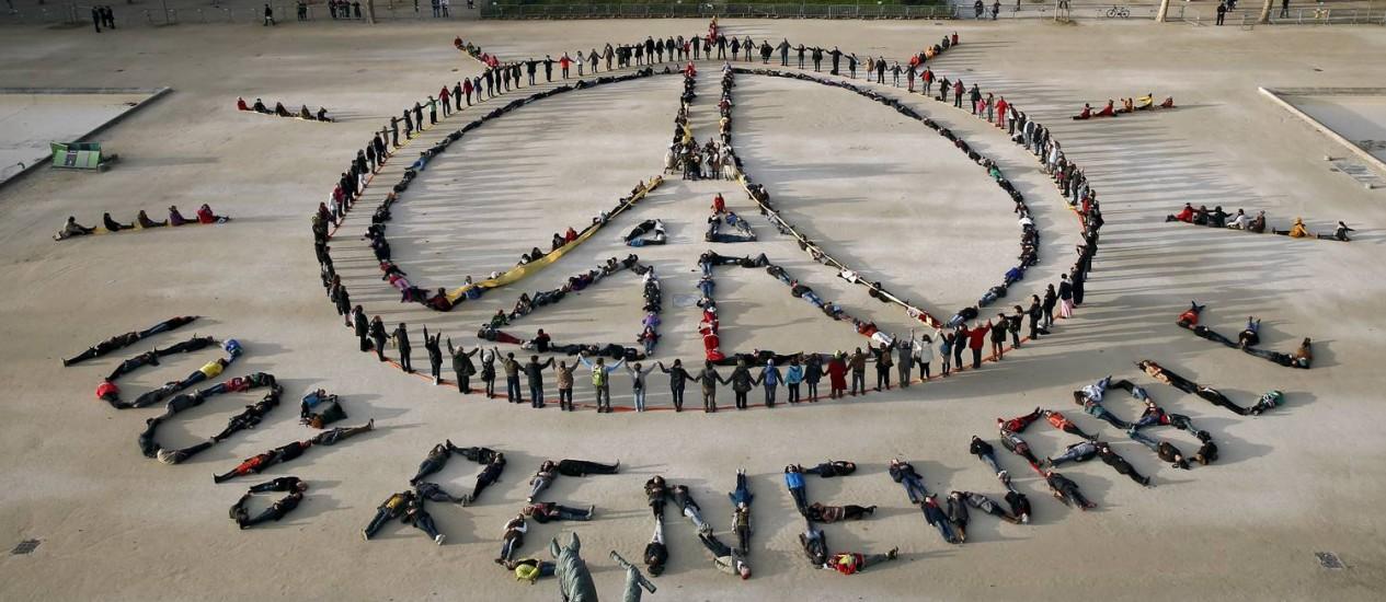 Centenas de ambientalistas fazem com seus corpos o símbolo da paz e pedem energia renovável perto da Torre Eiffel em Paris, num recado aos conferencistas Foto: BENOIT TESSIER / REUTERS