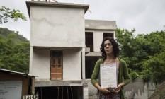 Documentos. Raquel mostra as certidões emitidas pelo Inea em 2013 Foto: Hermes de Paula / Agência O Globo